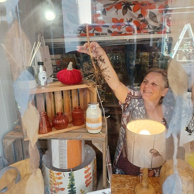 Owena at Luvit in Barmouth applying the finishing touches to her Autumn 2021 window display