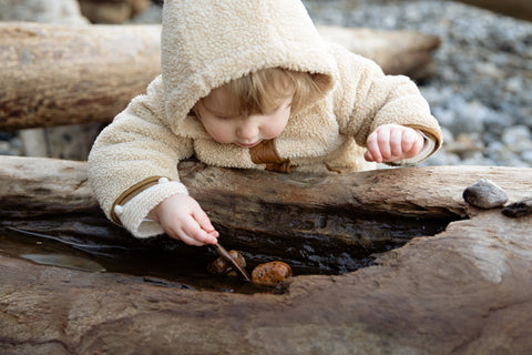A baby picking up stones with a spoon