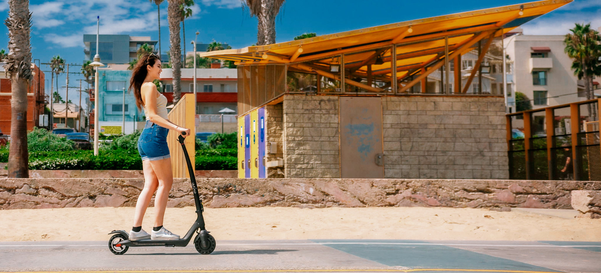 Woman riding Wire Ohm Electric Scooter on Los Angeles Beach boardwalk