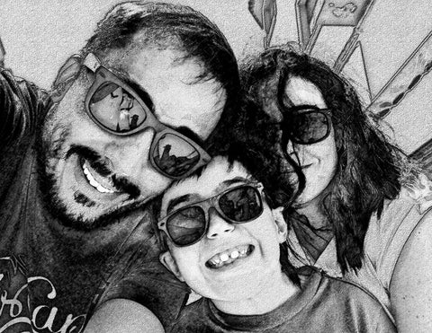A family takes a selfie together. The image is edited to give a pencil, or sketch, effect.