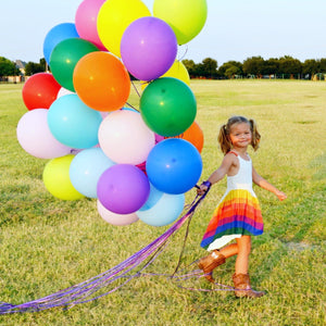 Girl holding rainbow balloons in rainbow dress for toddlers and kids with cowboy boots