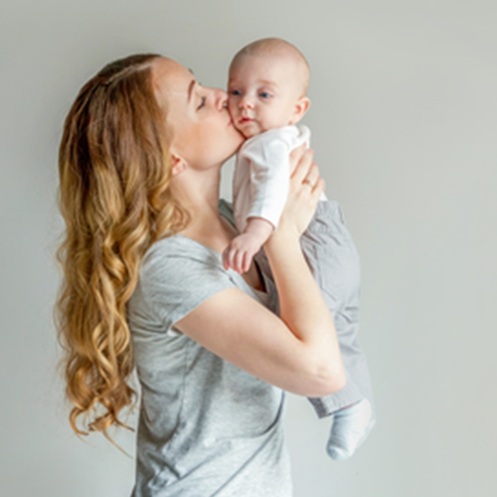Woman holding up and kissing baby