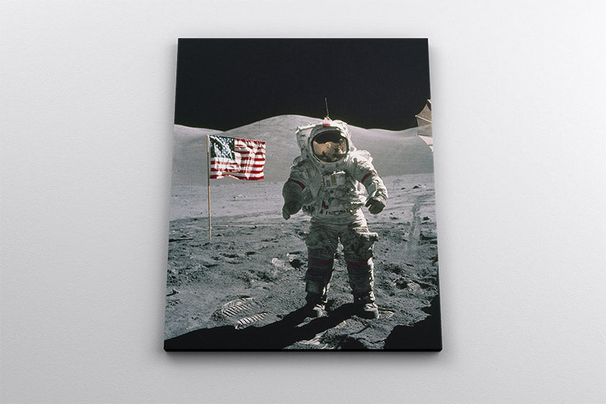 Apollo 17 astronaut Eugene Cernan on the surface of the Moon, standing next to an American flag. Canvas wall art in room.