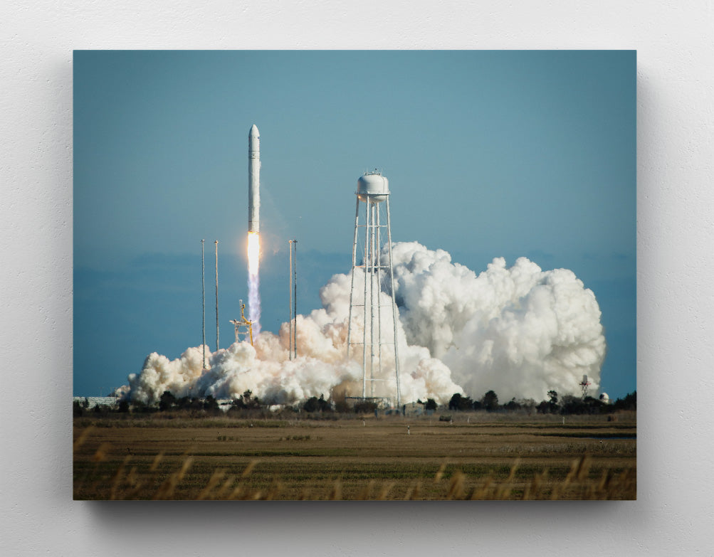 Antares A-One rocketship launching in field next to water tower, NASA image. Canvas wall art in room.