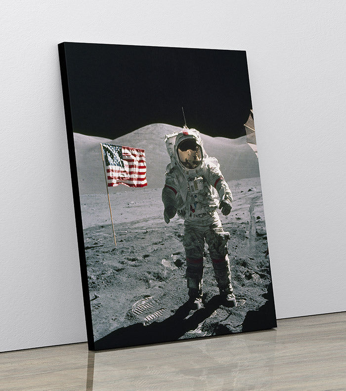 Apollo 17 astronaut Eugene Cernan standing on lunar surface next to American flag. Canvas wall art in room.