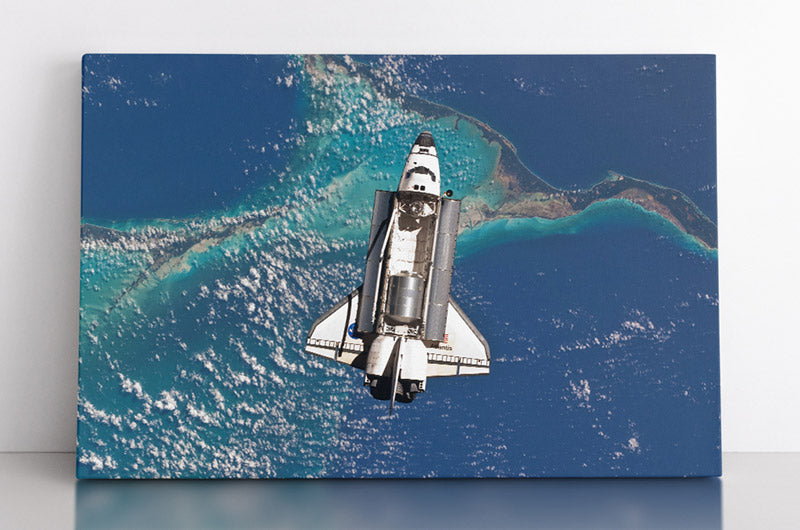 Space shuttle Atlantis in outer space, viewed above Earth, with ocean & islands below. Canvas wall art in room.