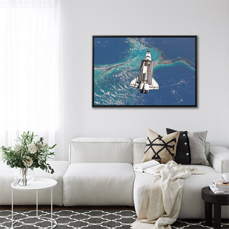 Space shuttle Atlantis above Earth, with doors open & payload visible. Perspective shot look down at ocean & islands below. Framed canvas wall art in living room.