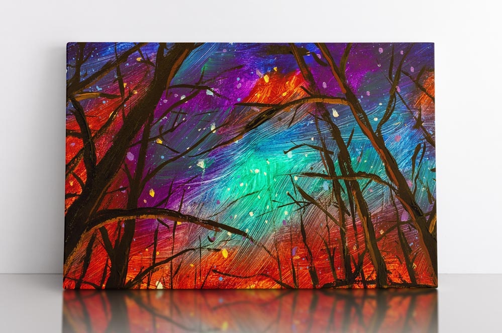 Colorful painting of night sky, as seen through the trees in a forest. Canvas wall art in room.