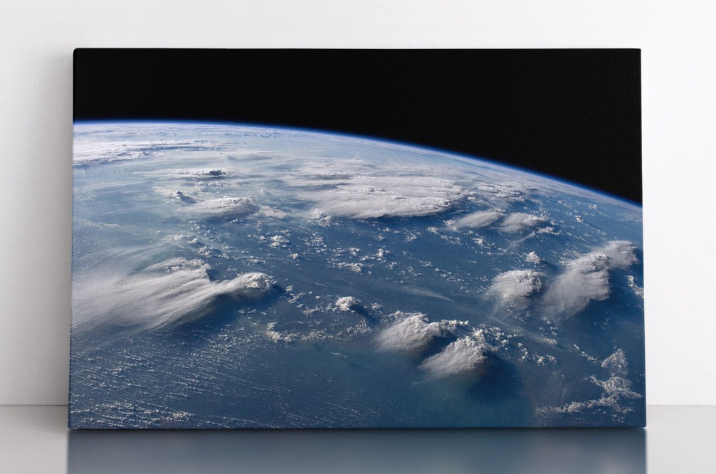 Planet Earth's horizon viewed from outer space showing oceans & clouds, canvas wall art in room.