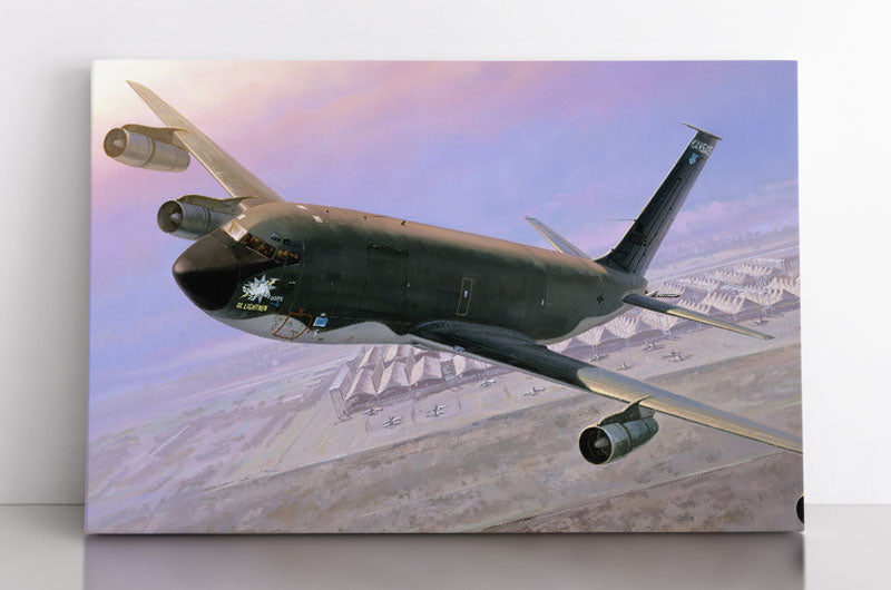 A military refueling tanker airplane flies above the Saudi Arabian desert and a military base with a beautiful sunset sky in the background. Canvas wall art in room.