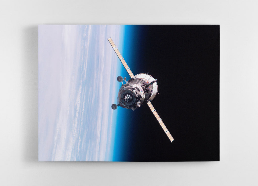 Soyuz TMA satellite in outer space above Earth with horizon in background, NASA image. Canvas wall art in room.