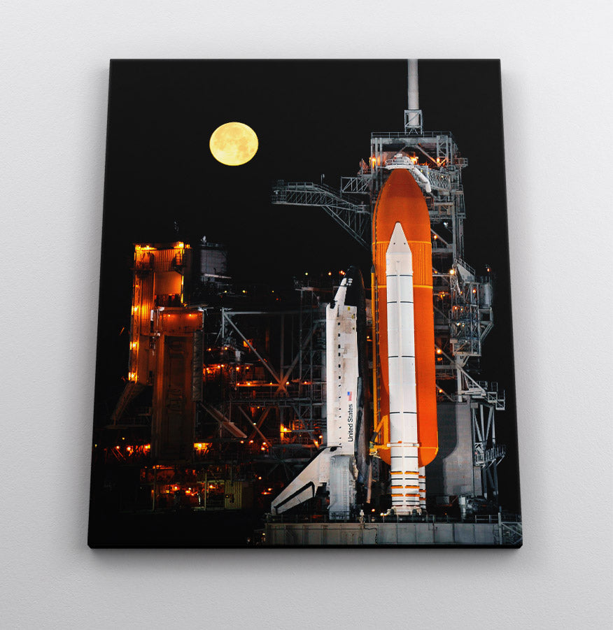 The Space Shuttle Discovery at night, with rocket boosters & moon in background. Canvas wall art in room.