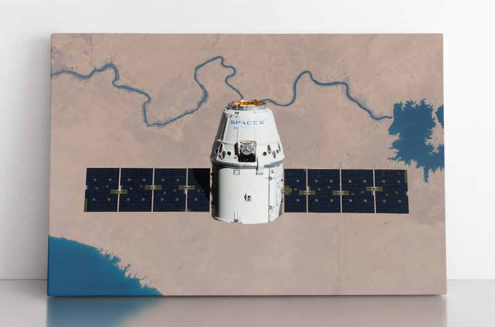 A Space-X satellite, photographed by NASA above Earth, looking down at desert and river below. Canvas wall art in room.