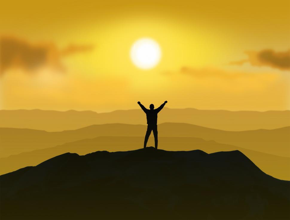 Victorious man stands at top of mountain with his arms raised