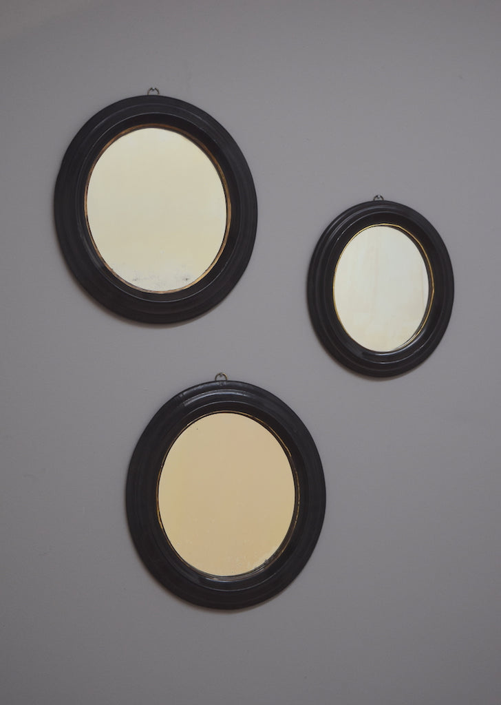 Trio of Ebonised Oval Mirrors