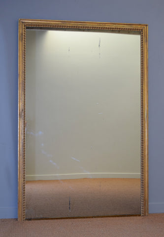 A large French Gilt Overmantel Mirror with Brass Base