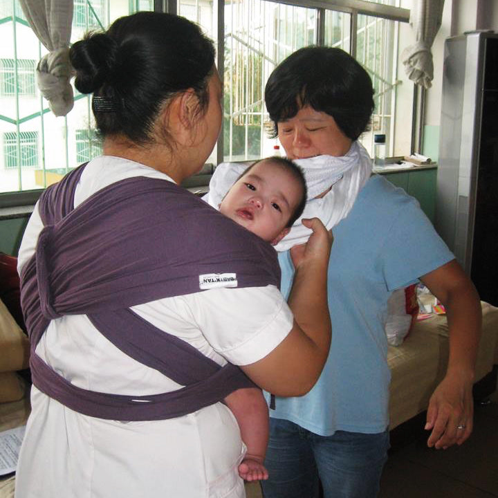 Teaching an orphanage caregiver how to use the Baby K'tan
