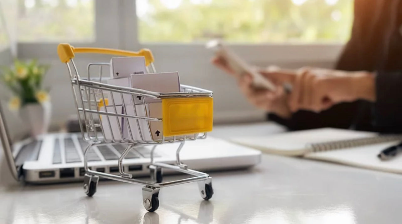 Miniature Cart Beside a Laptop and a Person Checking Mobile for Online Shopping