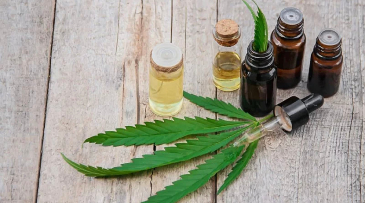 Cannabis extract in bottles and leaves on table