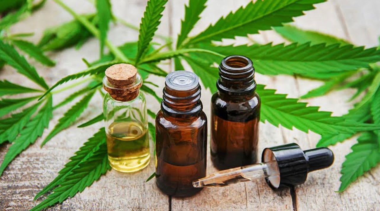 Bottles of cannabis extract and leaf on a wood