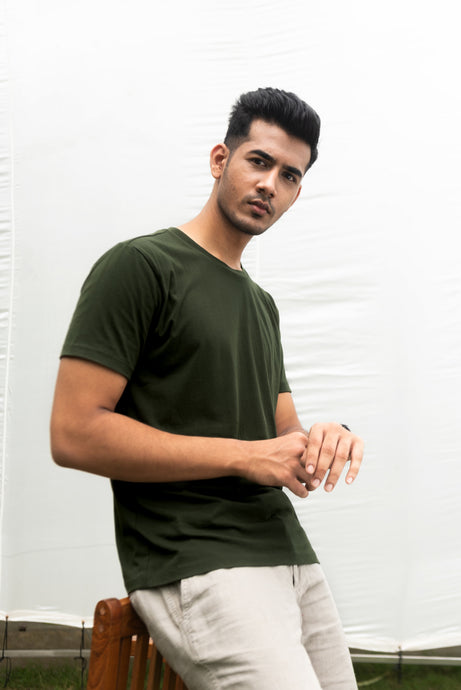 A man is standing, glanced up for a quick shot as he looked at his watch. He's dressed an Olive Green Tshirt made of 100% Organic Cotton and is wearing Beige Linen Pants. He looks fresh and great.