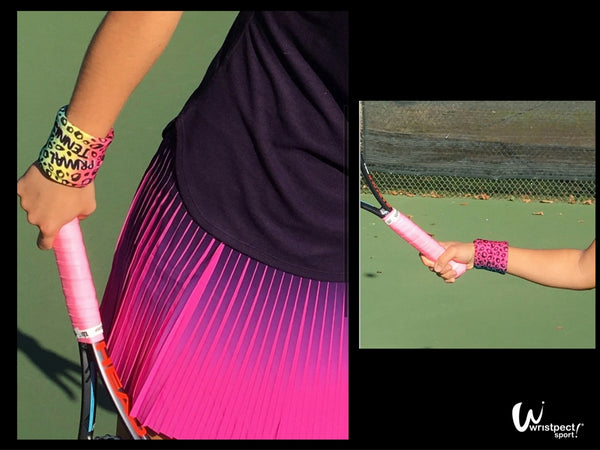 Close up of tennis players arms wearing Primal multi colored animal spotted wristband