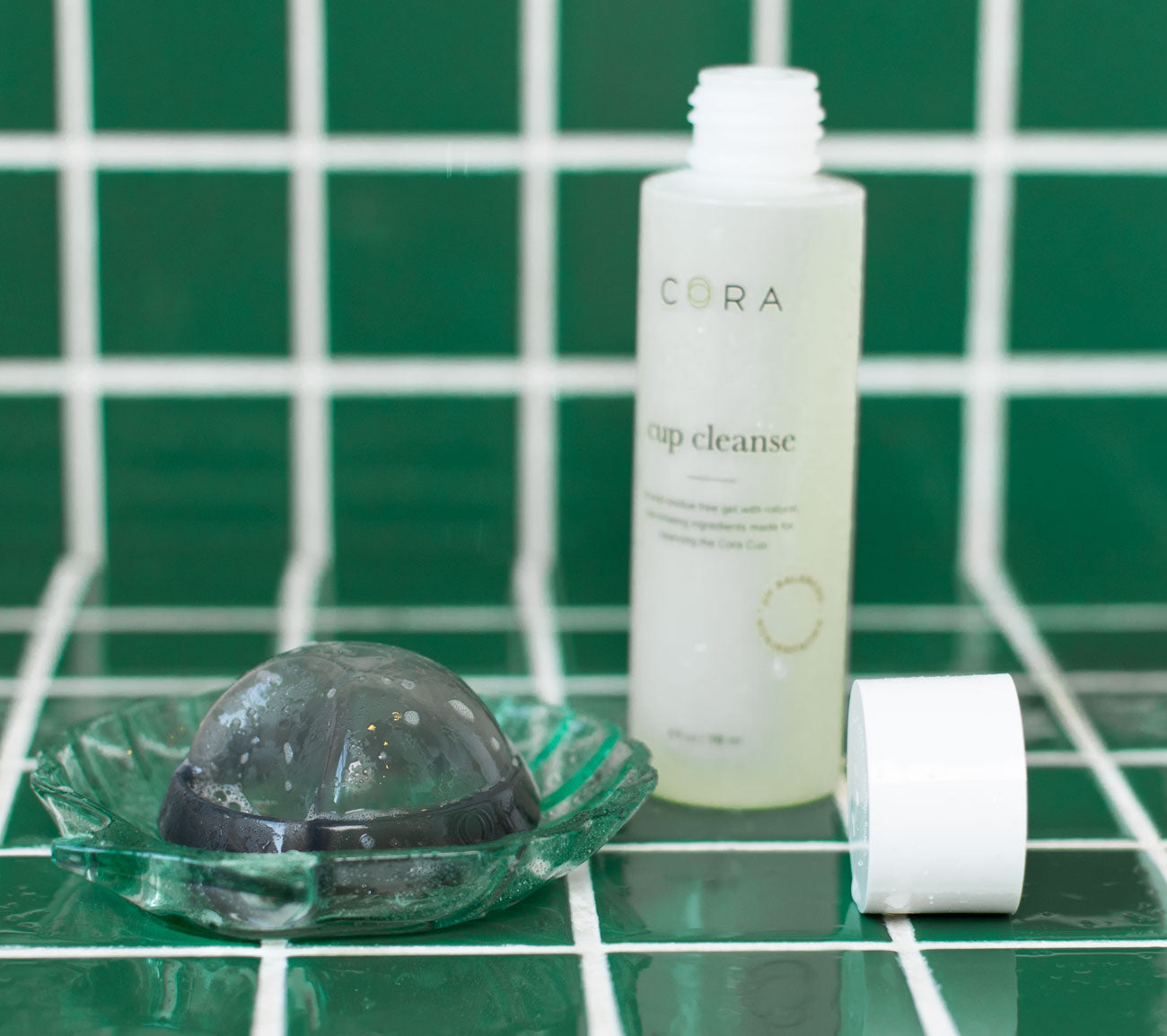 cora menstrual disc and cora cup cleanser on green tile