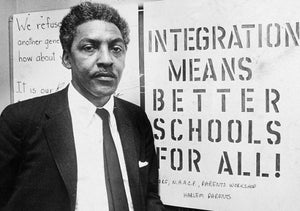 "Bayard Rustin next to a sign that reads ""Integration means better schools for all!"""
