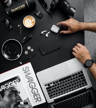 There is a laptop, a men's magazine, various gadgets and a cup of coffee on the table, and men's hands are also visible.