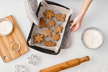 A baking dish with shaped cookies in it, a rolling pin, a cutting board and plates with ingredients