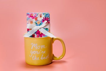 Yellow mug containing a gift with a white bow on a pink background