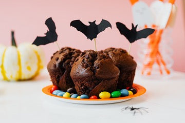 Cupcakes with bat on a stick decorated with colorful dragee