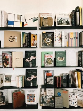 A white wall with black shelves containing books