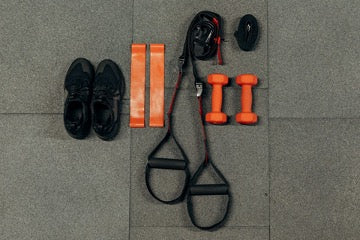 Black sneakers and black and orange fitness accessories on street tiles