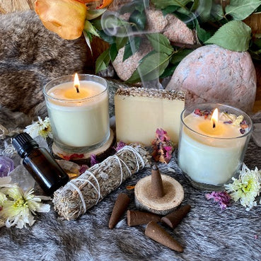 Stones, two burning candles and esoteric objects on a fur blanket