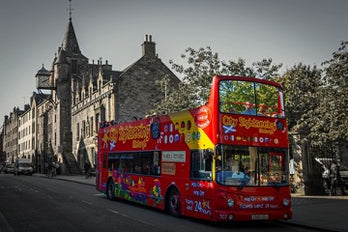 Red bus on the background of a historic building with towers