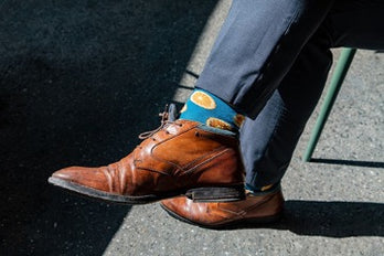 Male feet in blue socks and brown boots