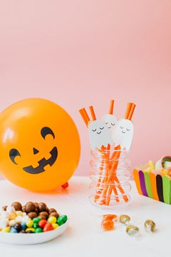On the table is a glass with haunted straws, a plate with multicolored dragees, and a Halloween-print balloon