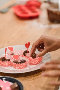 Hand takes chocolate candy from a plate