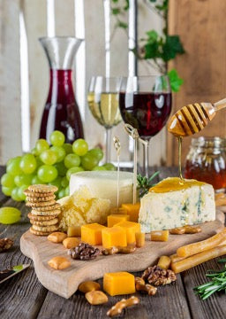 There are several types of cheeses, two glasses of wine, grapes and a jug on the table