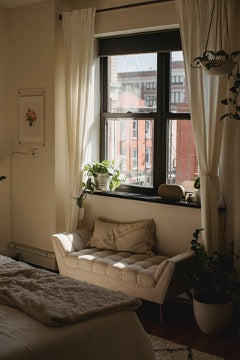 There is a white sofa in the window niche, white curtains hang on the window, and a painting on the wall