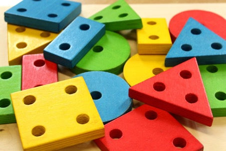 Multi-colored rectangles, squares, circles and triangles lie on a wooden surface