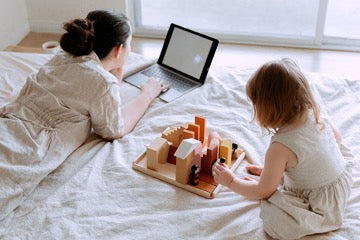 A woman lies and looks at a laptop, a girl sits next to her and plays with toys