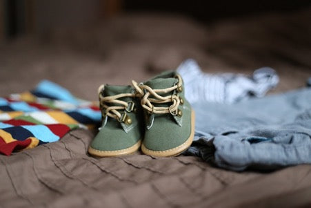 Green baby shoes with yellow laces stand on brown and blue fabric