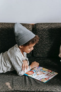 A child in a striped shirt and a gray hat lies on the sofa and looks at a book