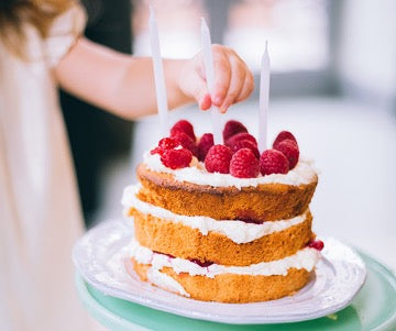Three-layer cake with raspberries on top and three white candles