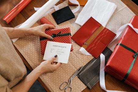 Hands hold a gift in a red gift box with a black bow and paper with the words