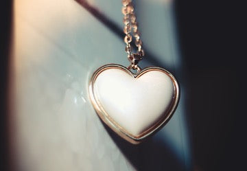 White heart pendant on a gold chain