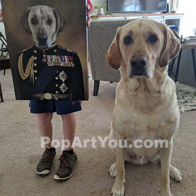 A man holds a portrait of a Labrador retriever, depicted in a historical veteran costume, and a Labrador retriever sits nearby