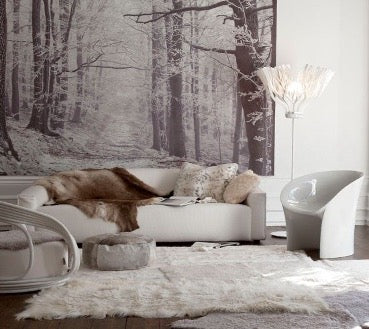 There is a white sofa with brown fur and a carpet of white fur on the floor in the room